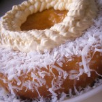 Tropical vanilla pineapple cake with mango coulis and whipped cream and coconut